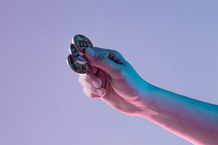 mão segurando três moedas de BitCoin
