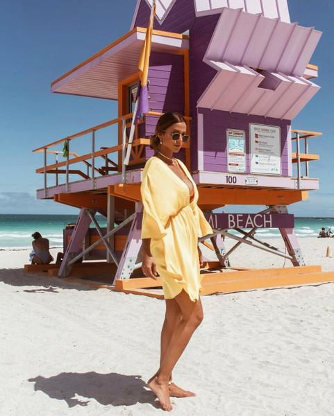 Aparece Kerline posando com um look elegante. Ao fundo, aparece o mar e uma cabana de praia.