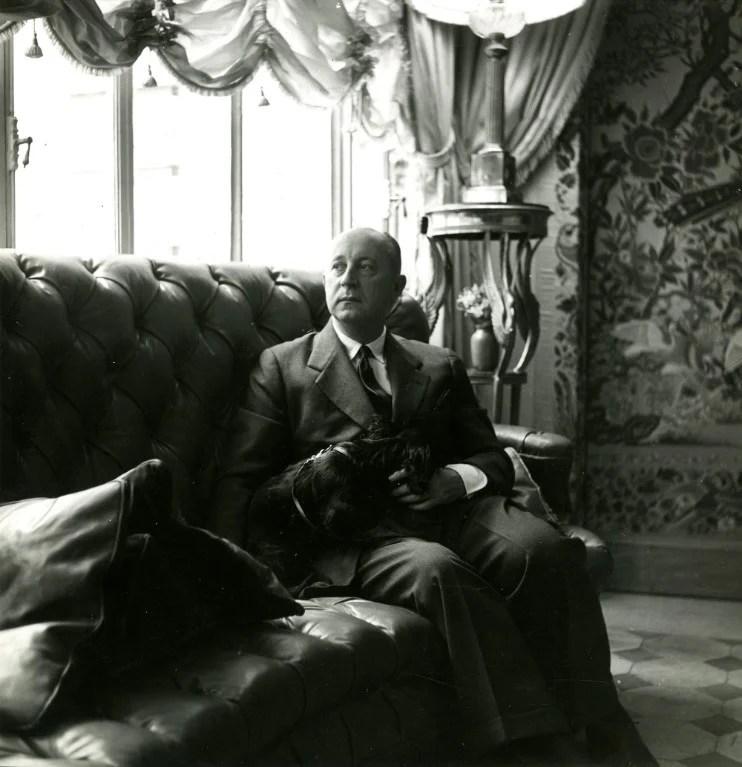 Christian Dior com o seu cachorro no seu apartamento, em Paris, em 1950.