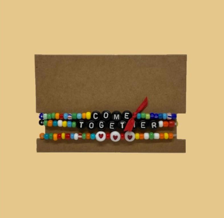 """Conjunto de pulseiras coloridas com a frase """"come together"""", de Roxanne Assoulin, para a inauguração do governo Joe Biden e Kamala Harris."""