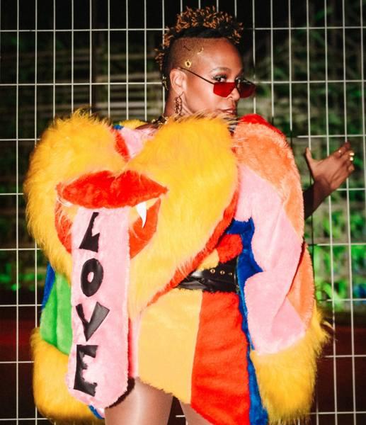 """Na foto aparece a cantora Karol Conká posando para foto em frente à uma grade. Ela veste um casaco que está escrito """"Love"""""""
