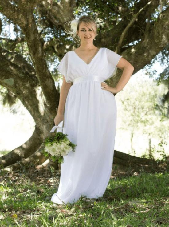 Vestido noiva plus size com faixa abaixo do busto e manga transparente.
