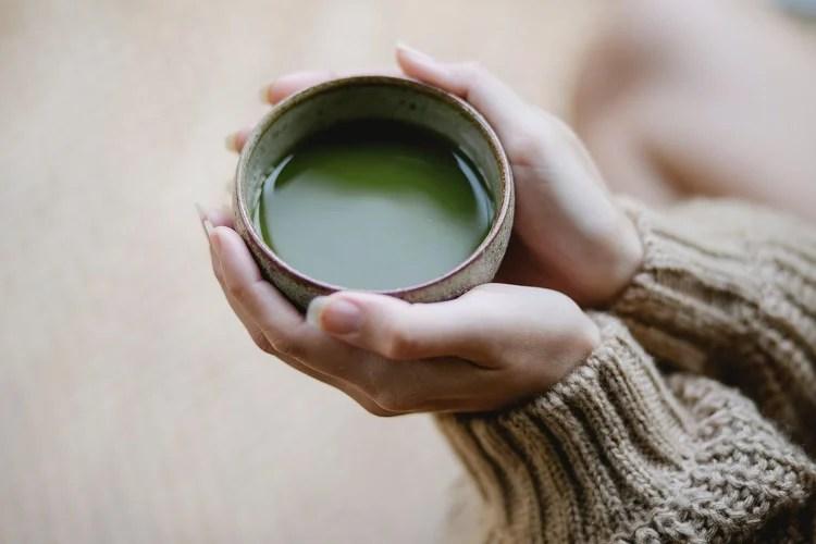 mulher segurando xícara de bebida quente