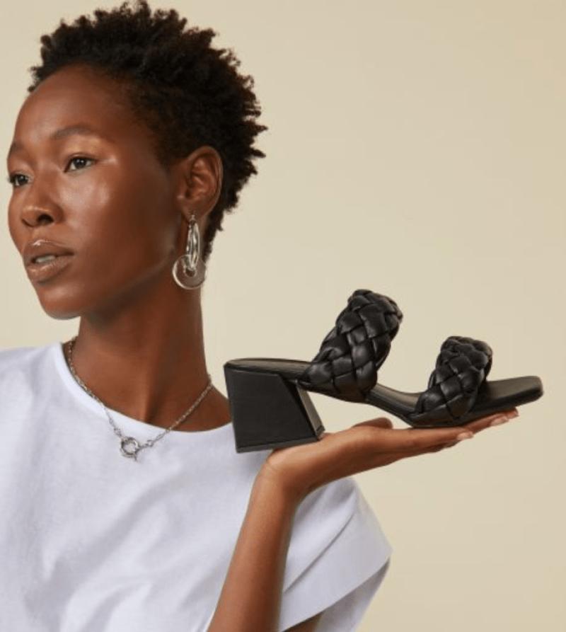 Modelo segura sandália com tiras e salto assimétrico
