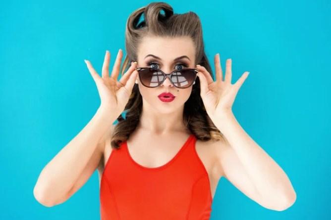 mulher de vestido vermelho abaixando o óculos
