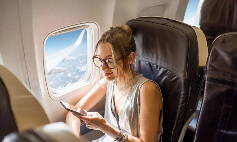 mulher no avião com celular - vender milhas