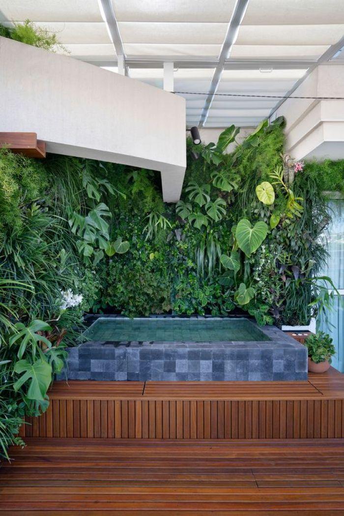 Parede com plantas e piscina quadrada.
