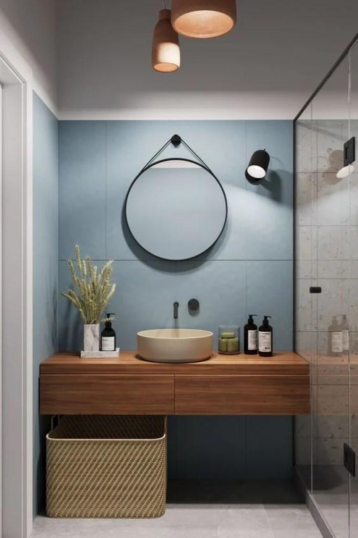 Parede azul com espelho redondo