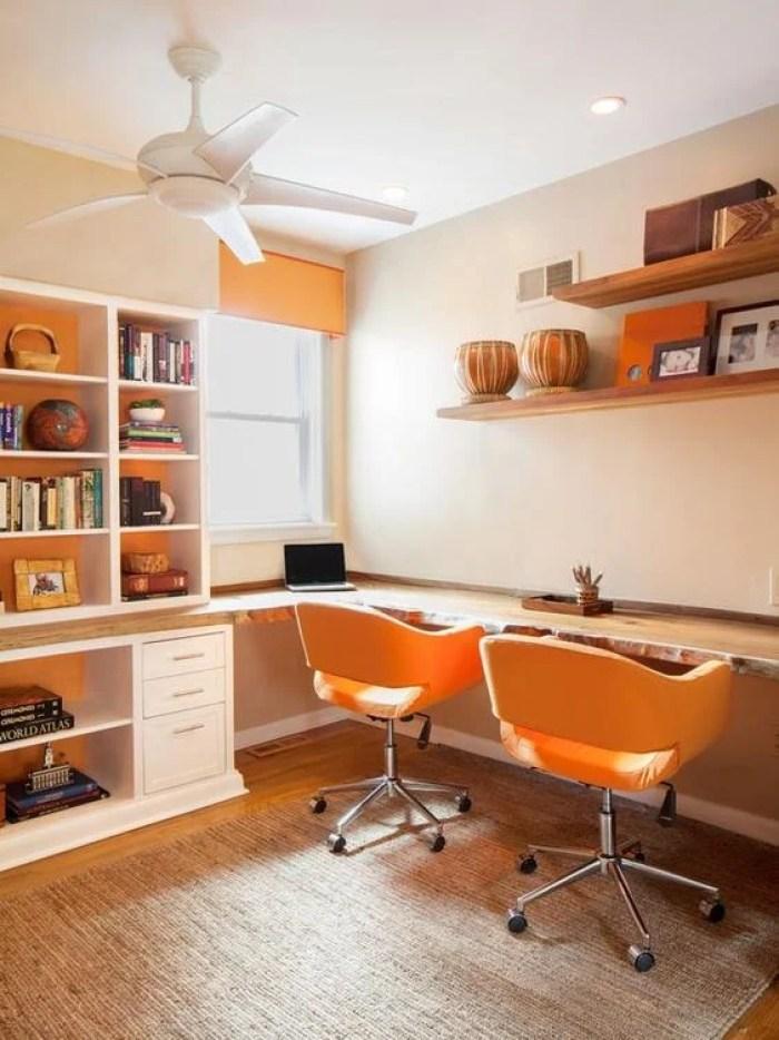 Escritório duplo com cadeiras laranjas.