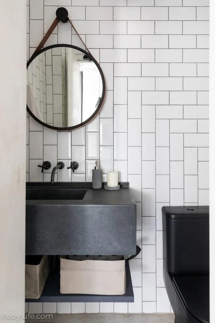 Espelho redondo no banheiro.