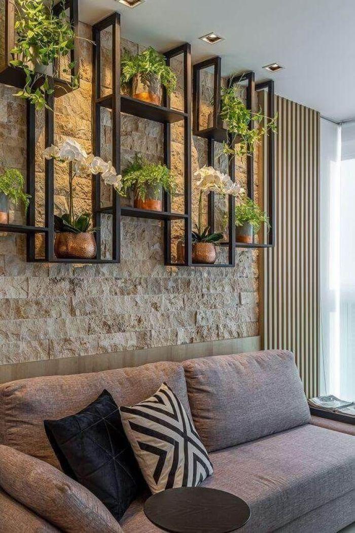 Sala com parede de pedra e plantas.