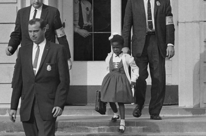 A menina Ruby Bridges, de 6 anos, a ser escoltada em New Orleans em 1960 diante do protesto de pais e outros cidadão (ela foi a primeira criança negra a entrar em um escola de brancos nessa região).