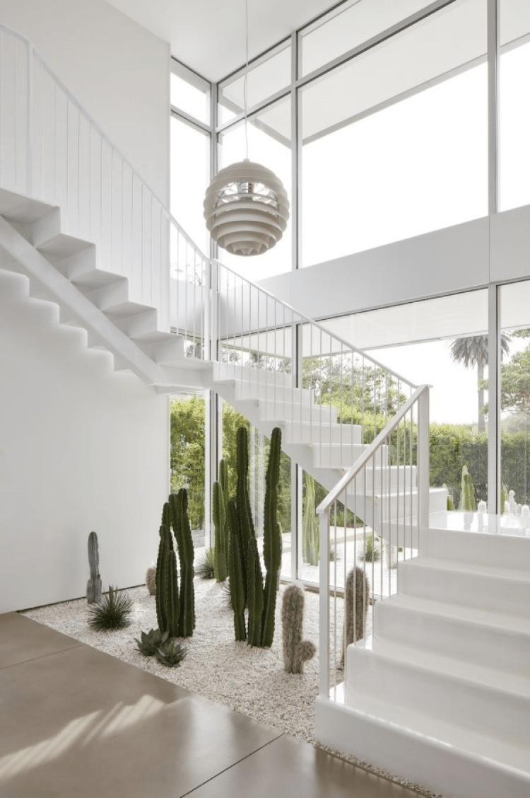 Jardim de inverno embaixo da escada branca.