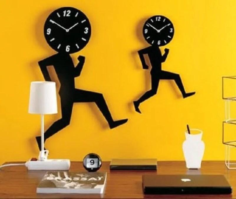 Parede amarela com relógio preto.
