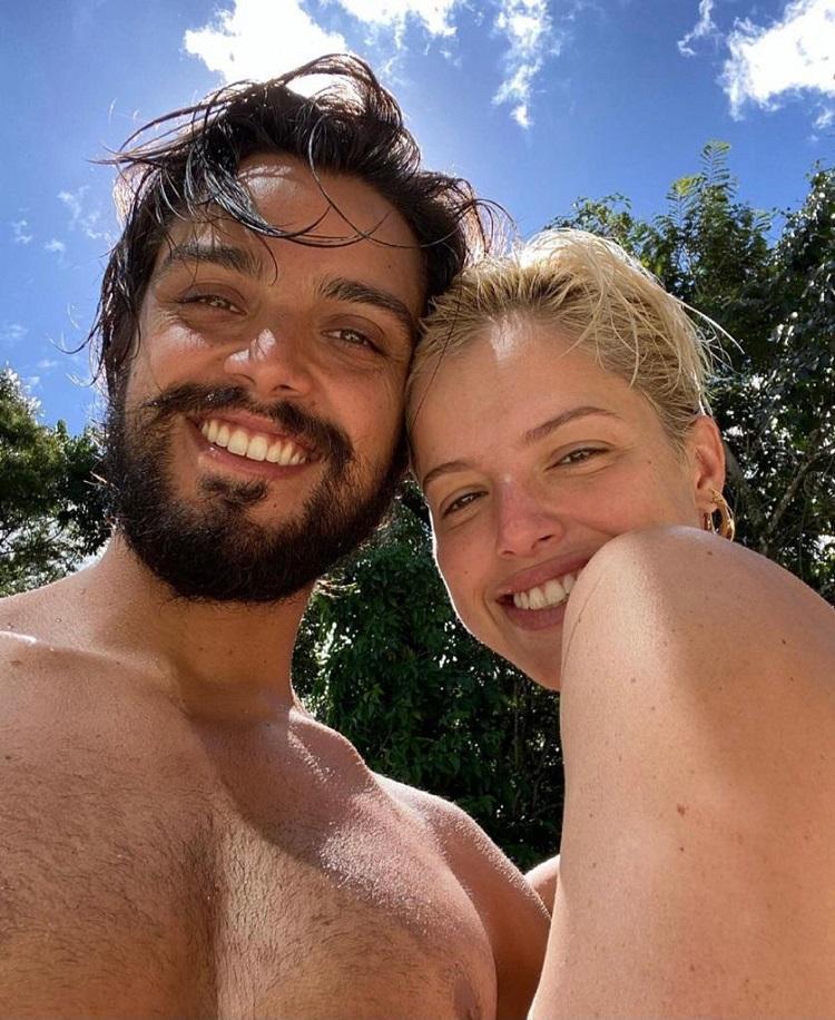 Rodrigo Simas e Agatha Moreira com rostinhos colados, de roupa de praia, com um dia lindo atrás