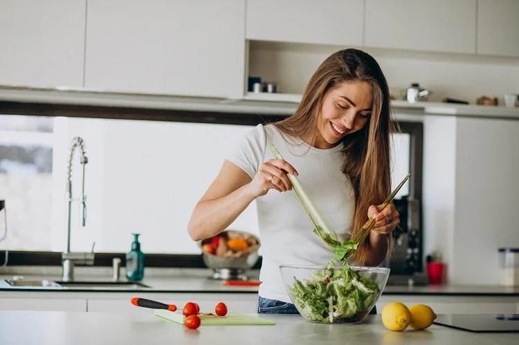 mulher sorridente temperando salada