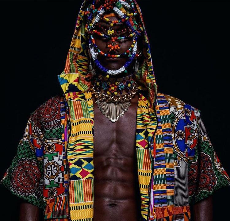 Modelo masculino com blusa com capuz colorida, e adereços coloridos no rosto.