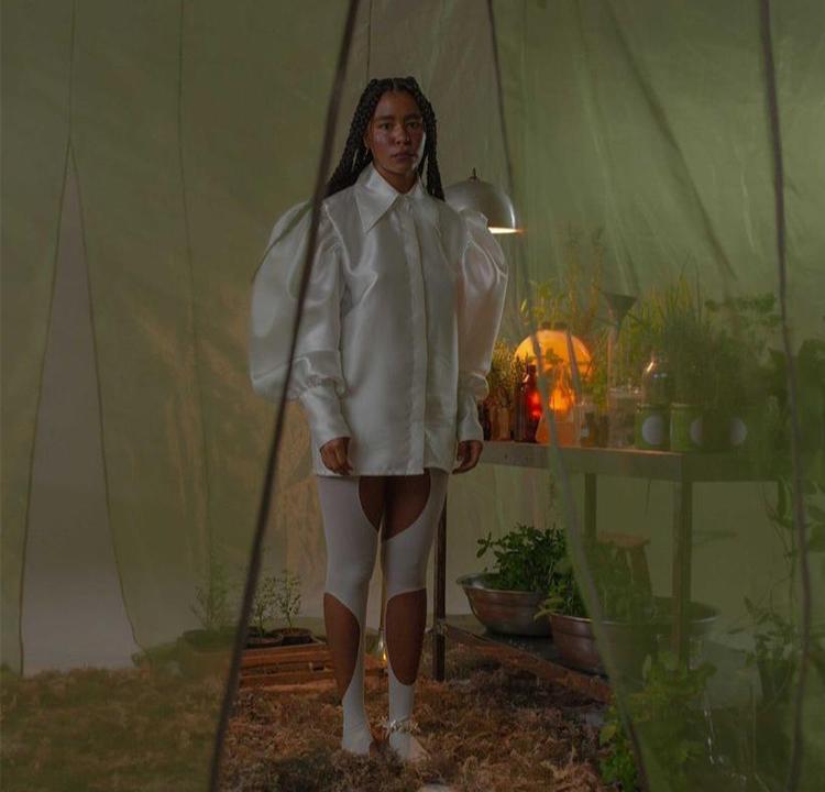 Modelo com blusa de mangas bufantes branca em ambiente verde cheio de plantas.