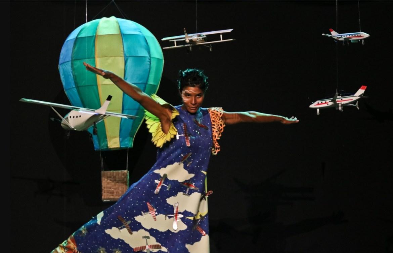Modelo vestindo vestido azul, posando com aviões e um balão miniaturas.