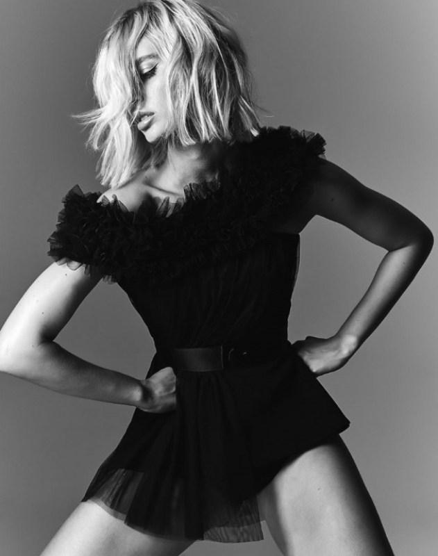 Foto em preto e branco de uma modelo posando com um vestido curto preto da campanha Verão 2021 de Vitor Zerbinato.