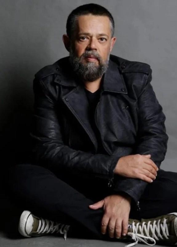 O estilista Vitor Zerbinatto posando sentado no chão.