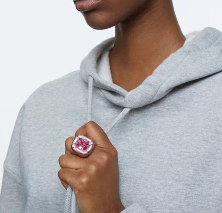 Foto de uma modelo usando um anel grande e rosa na mão direita.