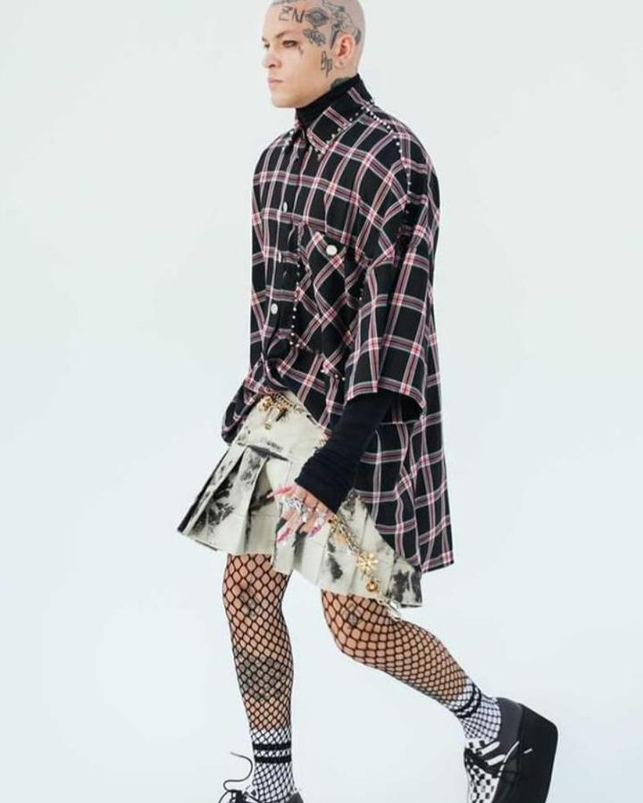 Modelo usa camisa xadrez, com saia curta metálica.