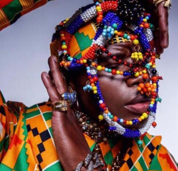 Modelo com adereços coloridos no rosto.
