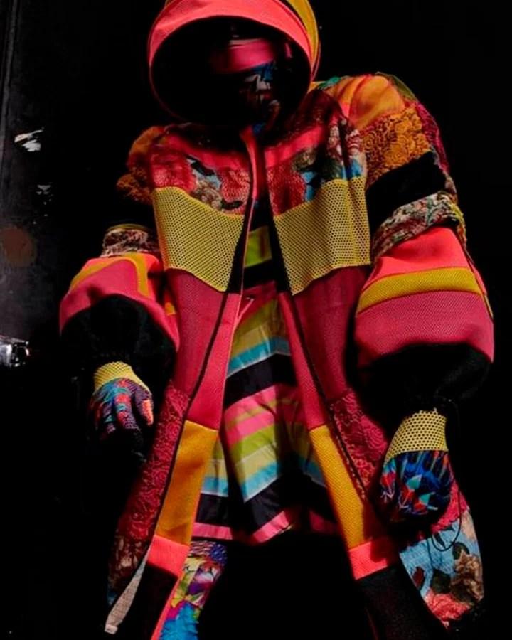 Modelo usa máscara e casaco de capuz coloridos combinando.