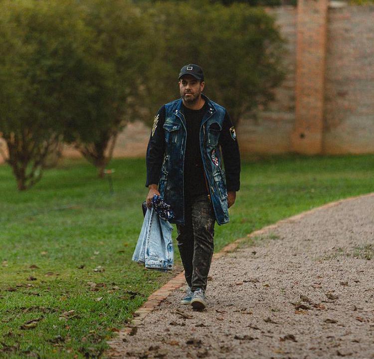 A foto do empresário João Foltran andando por um parque, carregando um par de jeans na mão esquerda.