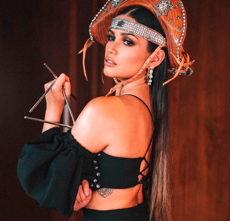 Foto de Juliette Freire de lado, com calça e top pretos e chapéu de cangaceiro, segurando o instrumento triângulo. Dá para ver uma parte da tatuagem dela nas costelas.