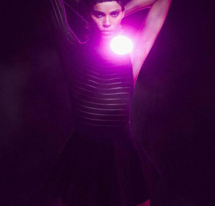 Modelo usando um vestido preto, com uma luz forte e roxa atrás dela.
