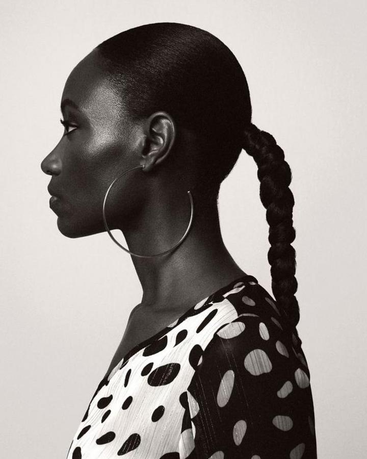 Modelo em perfil. Ela usa uma blusa de bolinhas e brinco argola grande. Foto em preto e branco.