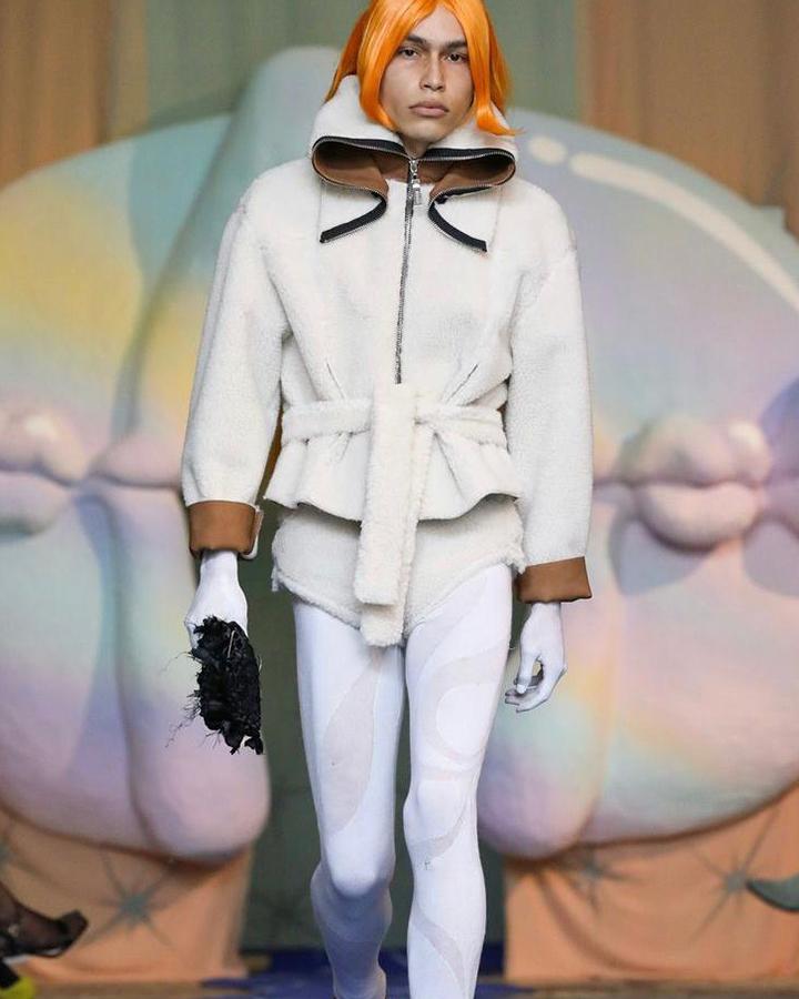 Modelo com peruca laranja usa legging branca e casaco felpudo também branco.