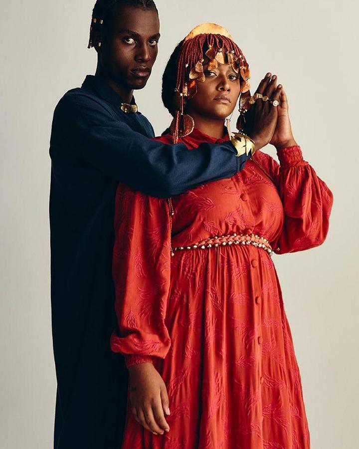 Casal de modelos, ele usa uma blus aazul, ela usa um vestido vermelho.