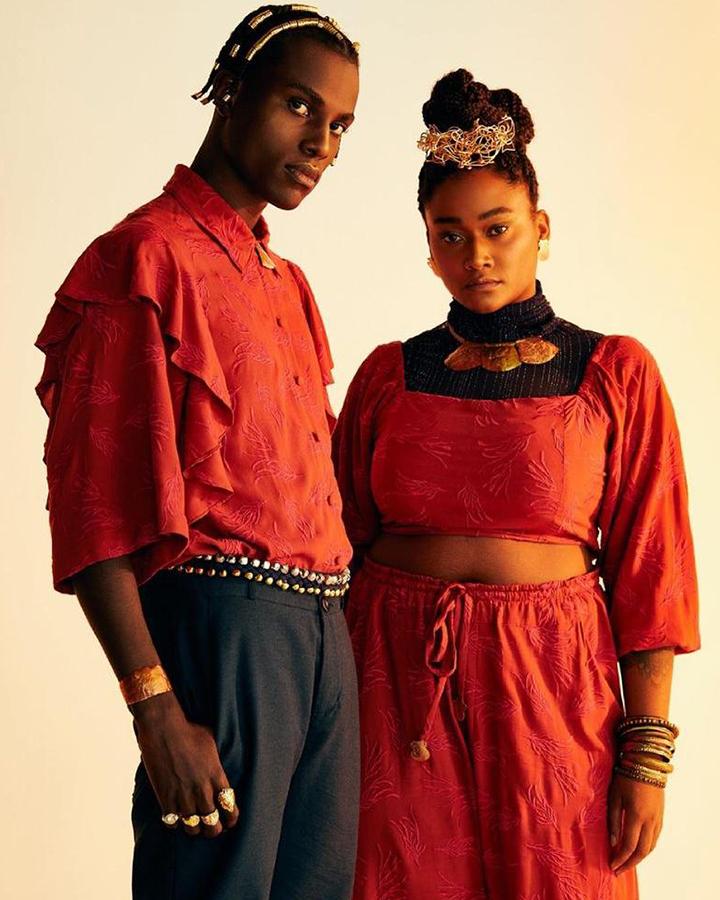 Casal de modelos. Ele usa uma blusa vermelha e calça escura. Ela usa blusa e calça vermelhas.