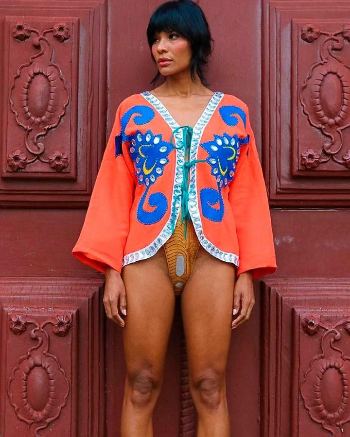 A modelo Suyane Moreira com uma jaqueta salmão e axul por cima de um maiô amarelo