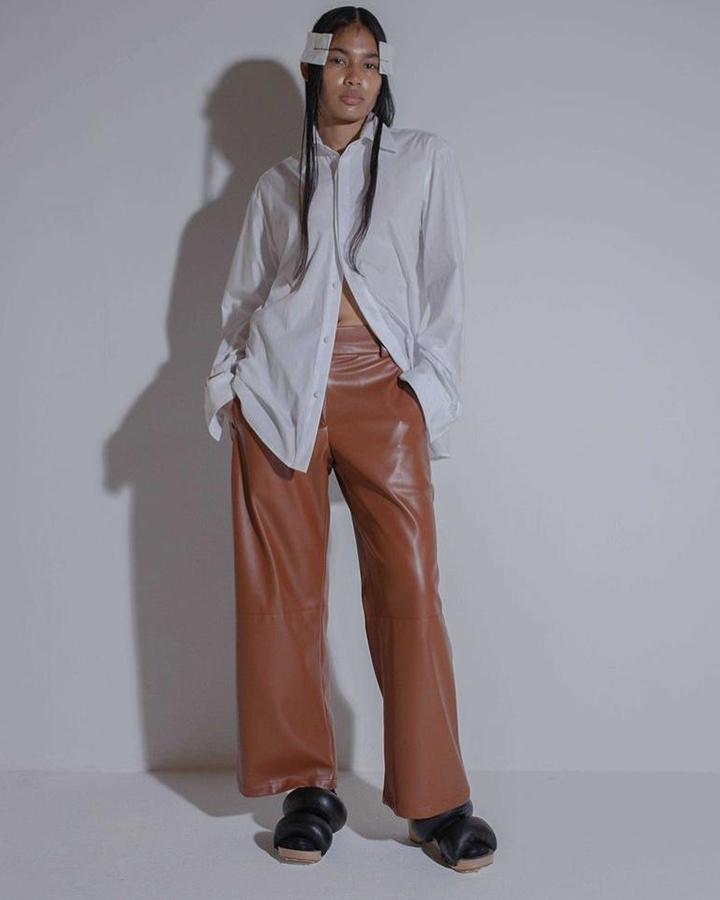 Modelo com calça marrom e blusa de botão branca