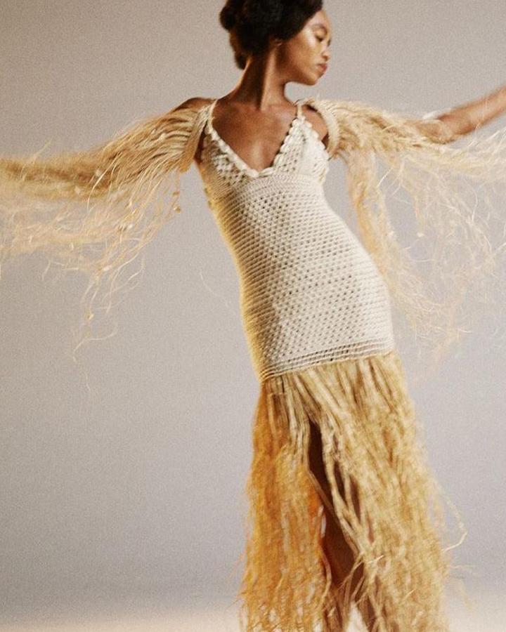 Modelo com um vestido de tricot bege com detalhes em palha.