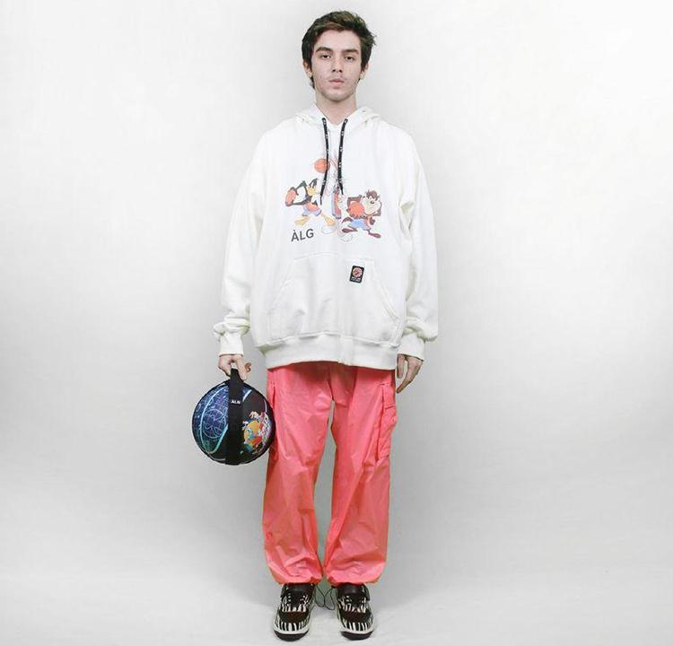 Modelo com moletom branco e calça larga rosa. Ele segura uma bola de basquete azul
