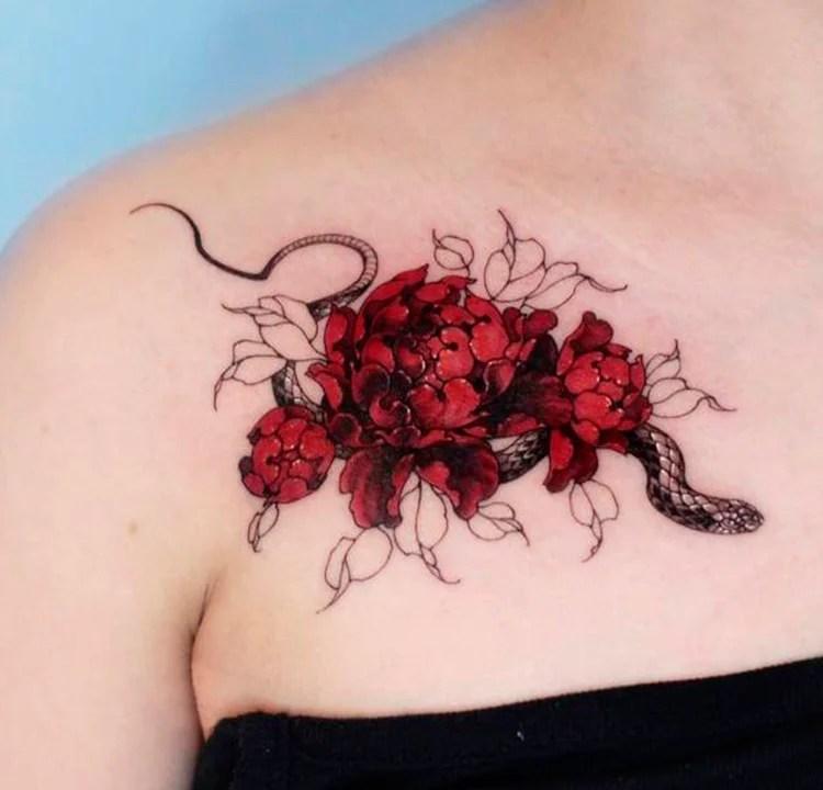 A foto de uma tatuagem de uma cobra cercada de flores vermelhas.