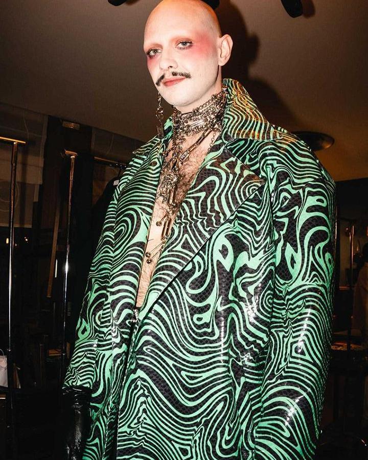 Modelo usando terno verde com padrão preto.