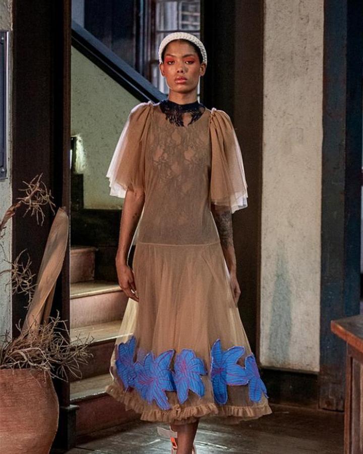 Modelo usando um vestido bege de mangas e detalhes azuis.