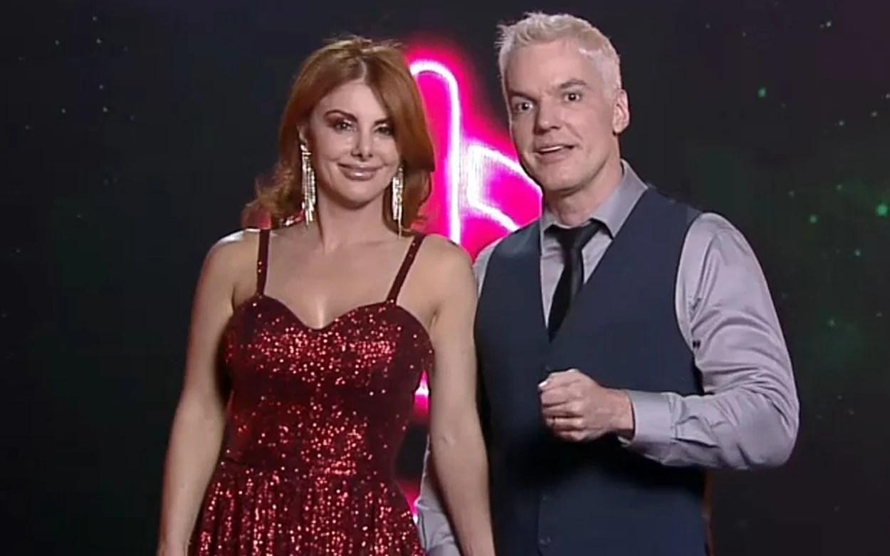 Deborah e Bruno em frente ao logo do Power Couple 2021