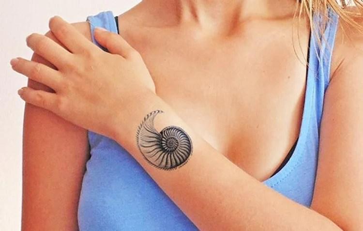 mulher com tatuagem de concha no braço