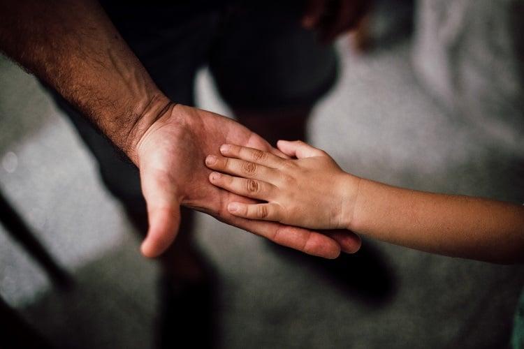 Foto de mão de um pai aberta, com a mão de seu filho por cima