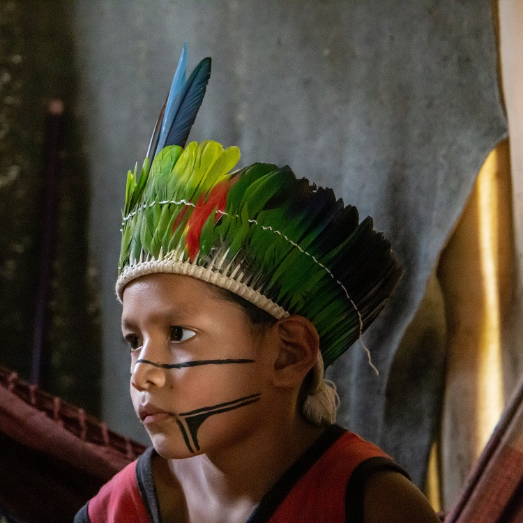 Menino usando cocar de povo indígena