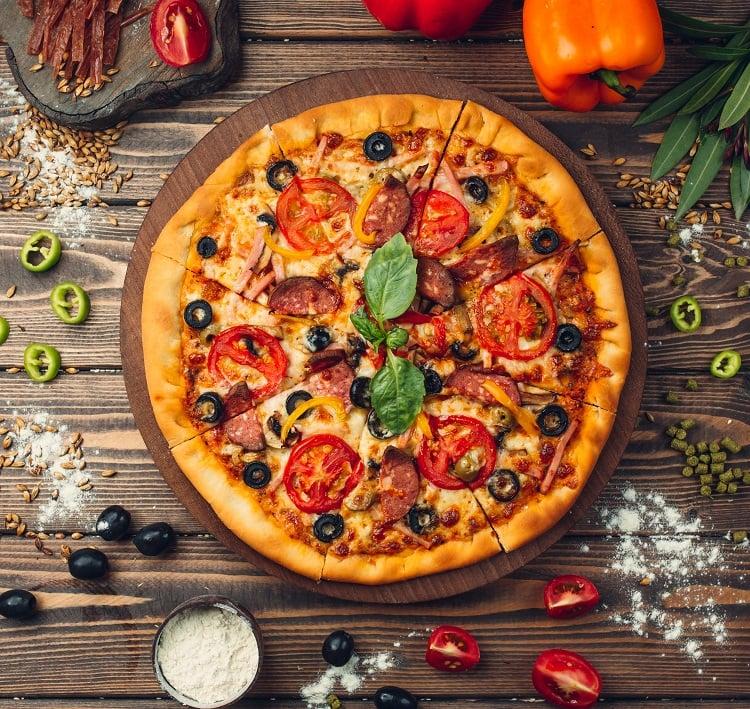 foto de pizza em bancada de madeira