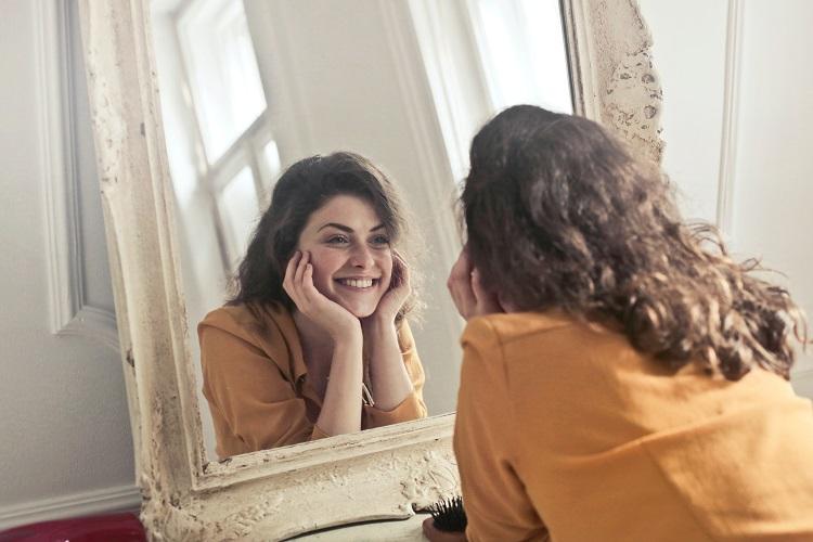 Foto de mulher sorridente com mãos no queixo se olhando no espelho