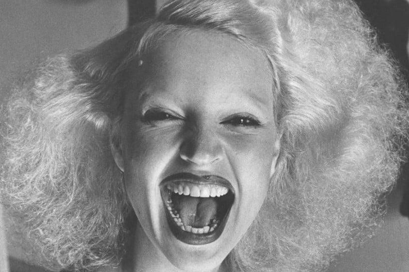 Retrato em preto e branco de Elke Maravilha jovem sorrindo de boca aberta.
